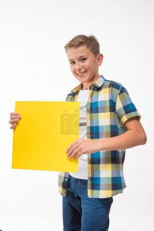 Photo for Emotional boy teenager in a plaid shirt with yellow sheet of paper for notes on a white background - Royalty Free Image