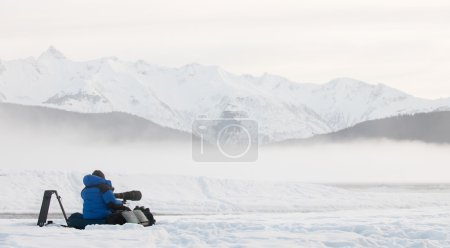 photographer on snow with tripod and camera
