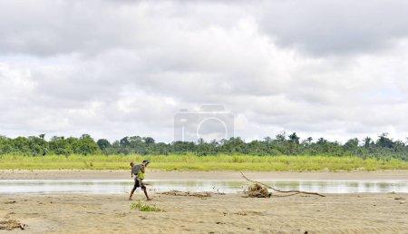 Photo pour INDONÉSIE, IRIAN JAYA, RIVIÈRE CÔTIÈRE À WILD JUNGLE NOUVELLE-GUINÉE - 17 MAI : Femme de la tribu Korowai avec bébé sur le dos va sur les hauts-fonds sablonneux de la rivière sauvage. Nouvelle Guinée, Indonésie. 17 mai 2016 - image libre de droit