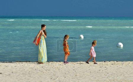 Photo pour Vacances d'été. Mère et filles mignonnes marchant sur la plage de sable fin. fond bleu océan. Cuba. Caya Coco - image libre de droit