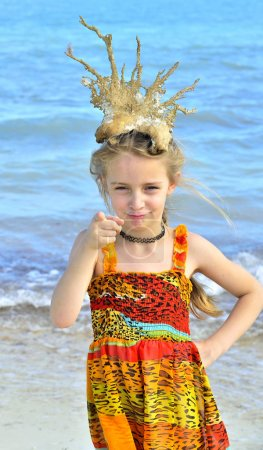 Portrait of a little girl with a coral crown on her head on the blue ocean background.