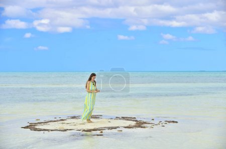 Woman in dress on a sandbank in the ocean. Adorable young girl on sandy beach . Young lady posing on beach. Outdoor relax leisure concept. Cuba. Caya Coco.