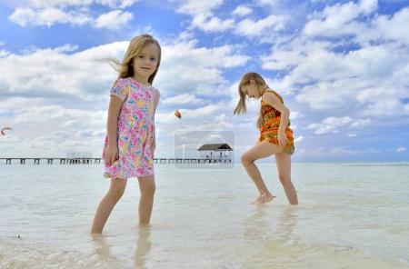 Cute little girls on sandy beach in sunset light. Cuba. Caya Coco.
