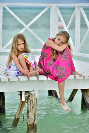 Little girls in colorful dress on the white wooden pier near the ocean. Cuba. Caya Coco. Beach season.