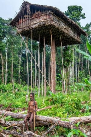 INDONESIA, NEW GUINEA, IRIAN JAYA, ONNI VILLAGE - JUNE 27: The Papuan from a Korowai tribe, live in the houses built on trees. On a background traditional Koroway house perched in a tree