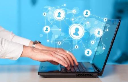 Foto de Cerca de la mano con el ordenador portátil y los iconos de red de medios de comunicación social - Imagen libre de derechos