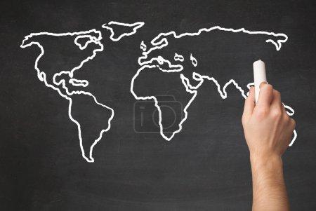 Photo pour Un professeur dessine la carte du monde sur un tableau noir avec une craie - image libre de droit