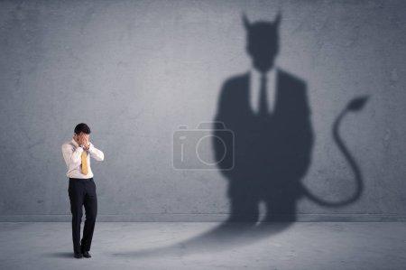 Homme d'affaires en regardant ses propres conceptions de shadow demon diable