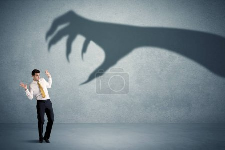 Photo for Business person afraid of a big monster claw shadow concept on background - Royalty Free Image