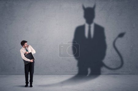 Business man looking at his own devil demon shadow concept