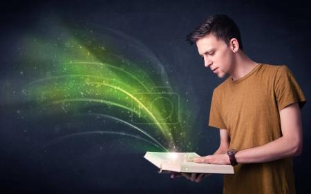 Casual young man holding book with green wave flyi...