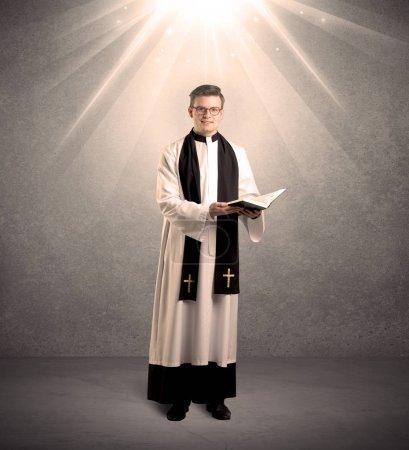 Foto de Un joven sacerdote religioso masculino vestido de blanco y negro dando su bendición, sosteniendo la sagrada biblia mientras es iluminado por fuertes rayos de luz que provienen del concepto de arriba - Imagen libre de derechos