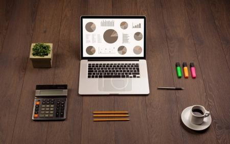 Photo pour Graphiques à secteurs icônes et symboles sur écran d'ordinateur portable avec accessoires de bureau - image libre de droit