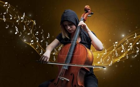Photo for Lonely musical composer with cello and sparkling musical notes around - Royalty Free Image