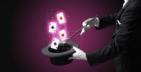 Foto de Mago blanco guantes prestidigitación jugando a las cartas de un cilindro con varita mágica - Imagen libre de derechos