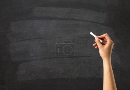 Photo pour Main féminine tenant de la craie blanche devant un tableau blanc - image libre de droit