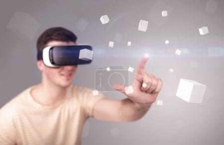 Photo for Young impressed man wearing virtual reality goggles with grey cubes around him - Royalty Free Image