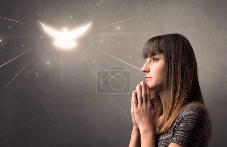 Photo pour Jeune femme priant sur un fond gris avec un oiseau scintillant au-dessus d'elle - image libre de droit