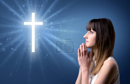 Photo pour Jeune femme priant sur un fond bleu avec une croix scintillante au-dessus d'elle - image libre de droit