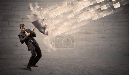 Photo pour Homme d'affaires protégeant avec parapluie contre le vent de papier concept - image libre de droit