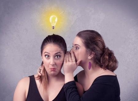 Photo pour Une jeune fille a une idée illustrée avec une ampoule lumineuse dessinée au-dessus de la tête, tandis qu'une amie murmure un secret dans son concept d'oreille . - image libre de droit