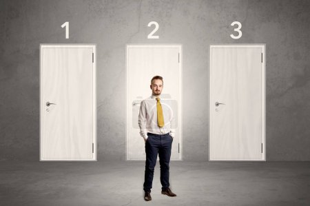 Photo for Businessman in grey room with three numbered white  door behind his bac - Royalty Free Image