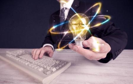 Geschäftsmann hält eine bunte Glühbirne in der Hand