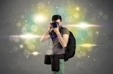 Photo pour Un jeune photographe amateur avec un appareil photo professionnel prenant des photos devant un mur gris plein de bokeh coloré et lumineux concept de lumières - image libre de droit