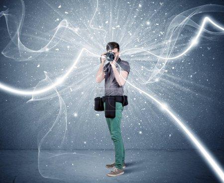 Photo pour Un jeune photographe amateur avec un équipement photographique professionnel prenant des photos devant un mur bleu avec un concept dynamique d'illustration de lignes blanches - image libre de droit