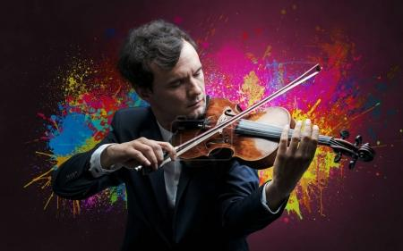 Photo for Young classical violinist musician with colorful splotch wallpape - Royalty Free Image