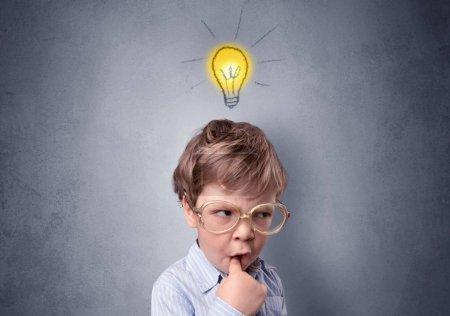 Photo pour Adorable petit enfant réfléchit devant un mur gris avec symbole d'idée au-dessus de sa tête - image libre de droit