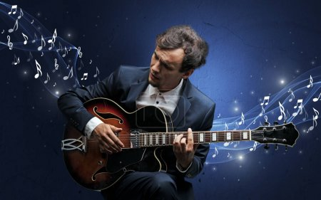Photo pour Compositeur de musique solitaire avec guitare et des notes de musique pétillantes autour - image libre de droit