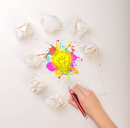 Photo for Female hand next to a few crumpled paper balls drawing a colorful lightbulb - Royalty Free Image