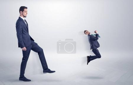 Photo for Small young man fired by his bos from his workplace with suitcase on his han - Royalty Free Image