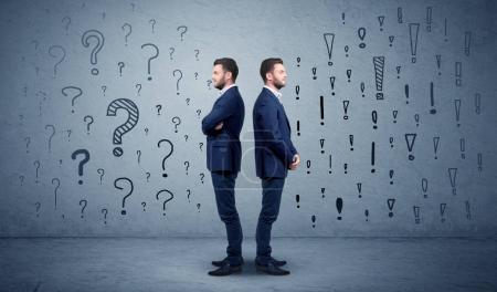 Photo for Young conflicted businessman choosing between two directions with question and exclamation marks - Royalty Free Image