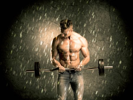 Photo for A handsome young body builder weightlifting while showing his muscular upper body in the rain concept - Royalty Free Image