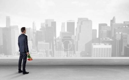 Photo pour Homme d'affaires debout avec le dos sur un toit avec des objets dans son han - image libre de droit