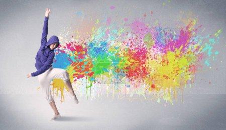 Photo pour Un danseur hip hop contemporain funky dansant devant un fond gris avec un concept éclaboussé de peinture lumineuse colorée - image libre de droit