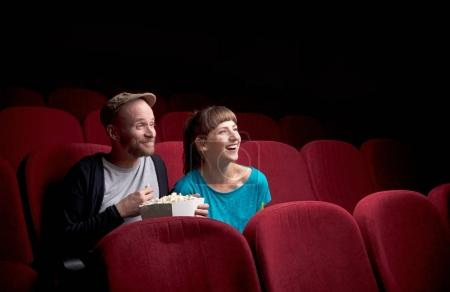 Photo pour Jeune couple mignon assis tout seul au cinéma rouge et s'amuser - image libre de droit