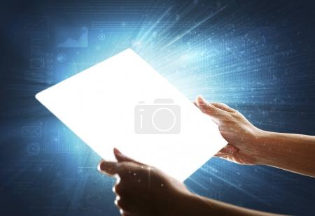 Photo for Young female hand holding a tablet with faded charts in the background - Royalty Free Image