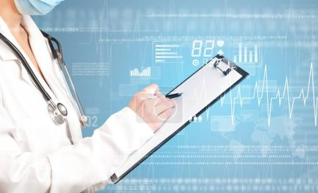 Foto de Doctora sosteniendo bloc de notas con fondo azul y gráficos relacionados con el corazón - Imagen libre de derechos