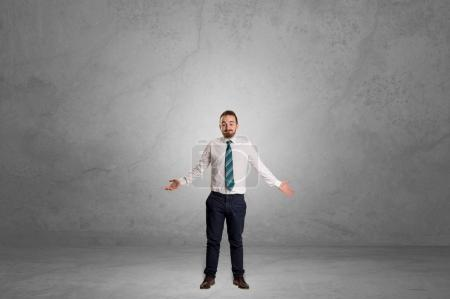 Photo for Alone handsome businessman standing in a dark empty room - Royalty Free Image