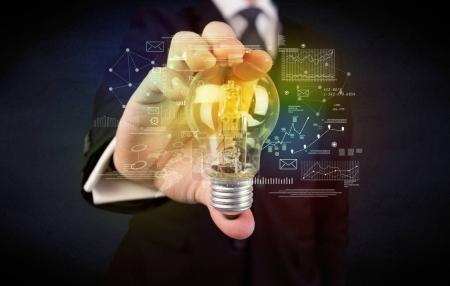 Foto de Una persona de negocios seria tiene un concepto de solución complejo ilustrado por la bombilla de cristal brillante en su mano con gráficos, números, líneas, cálculos . - Imagen libre de derechos