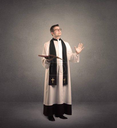 Photo pour Un jeune prêtre homme en noir et blanc donnant sa bénédiction devant un mur gris avec un concept de croix rayonnante . - image libre de droit