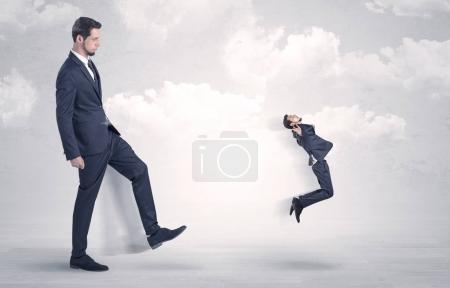 Photo for Big businessmen kicking himself as a small employee with cloudy backgroun - Royalty Free Image