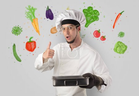 Photo for Bearded cook with colourful drawn vegetables on a white wallpape - Royalty Free Image