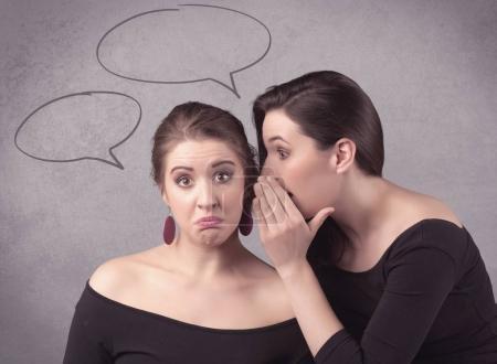 Photo pour Deux filles bavardant et partageant leur concept secret avec des bulles de chat dessinées sur le mur urbain de fond . - image libre de droit