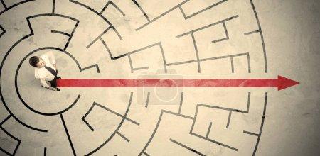 Photo pour Homme d'affaires debout au milieu d'un labyrinthe circulaire avec flèche rouge - image libre de droit