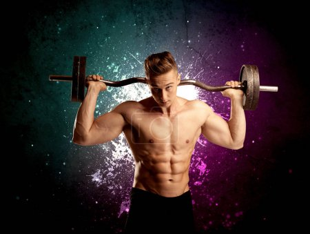 Photo for A sexy male fitness trainer showing his muscles and looking seductive with a weight in his hands in front of bright paint splash purple wall concept - Royalty Free Image