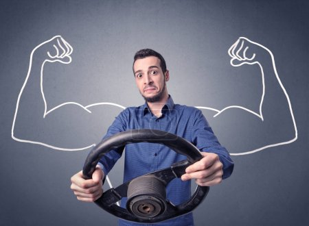 Photo for Young man holding black steering wheel with muscly arms drawn next to him - Royalty Free Image